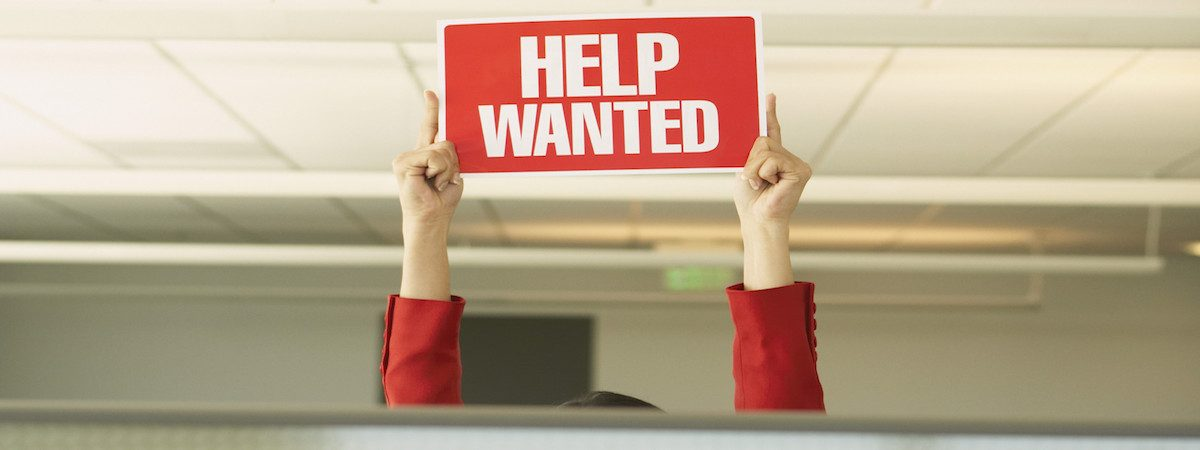 Businesswoman holding a ?Help Wanted? sign over partitions